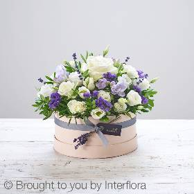 This beautifully presented hat box is skilfully arranged by Sandra's Florist and delivered by hand. Featuring a ivory large headed rose, white spray roses, purple freesia, a white lisianthus, purple statice, dried lavender and foliage, presented in a soft nude 'keepsake' hatbox trimmed with ribbon.