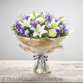 This is a stunning blue and white hand tied bouquet is the perfect welcome for a baby boy. Skilfully created by Sandra's Florist it features ivory large headed roses, purple freesia, blue iris, white lilies, purple lisianthus and complimenting foliage. It's finished and presented with beautifully gift packaging.