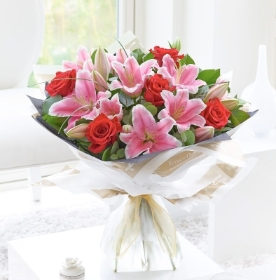 Truly a match made in heaven. A design of stunning large headed red roses teamed with beautiful scented Oriental lily . This bouquet is bound to impress your loved one . Created by our team of florists and delivered by hand contact free.