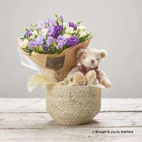 This Baby Boy Lilacs Bundle is the perfect gift to celebrate the birth of a new born baby. This delicate design features the finest white roses, scented freesia and purple lisianthus, complemented by glossy dark green foliage. These flowers are expertly arranged into a petite Hand tied bunch, perfect for Mum to enjoy. James Junior, a beautiful plush soft toy meeting all safety standards will surely become baby's favourite. These are paired together and presented in a useful soft woven jute basket. This will be carefully hand delivered by Sandra's Florist and will delight the new parents.