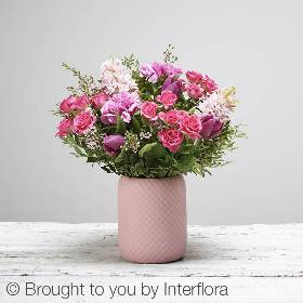 A beautiful jar bursting with fresh bright pink flowers, including pink hyacinths, purple tulips, cerise spray roses, cerise carnations and dainty filler flowers and complimenting foliage. The skilled florists at Sandra's will arrange the cheerful selection in a pink ceramic vase.