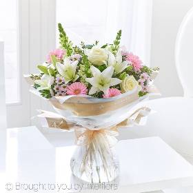 This exquisite bouquet is a naturally stylish yet informal display that looks particularly feminine the choice of flowers really add to the luxuriousness of this gift. Sandra's Florist will select flowers including a white LA lily, a white large headed rose, pink spray chrysanthemums, white antirrhinums and pink germini, hand-tied with eucalyptus and salal, beautifully wrapped and presented in Gift Packaging.